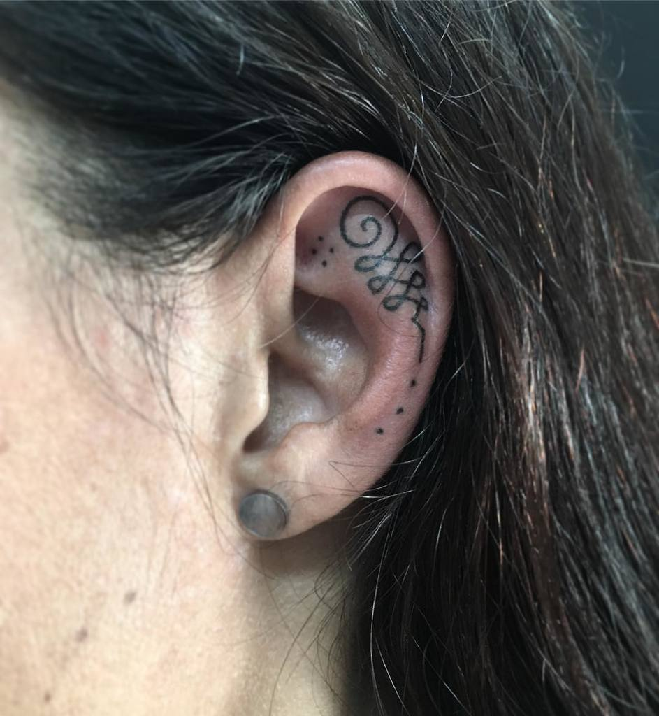 Unalome tattoo inside ear.