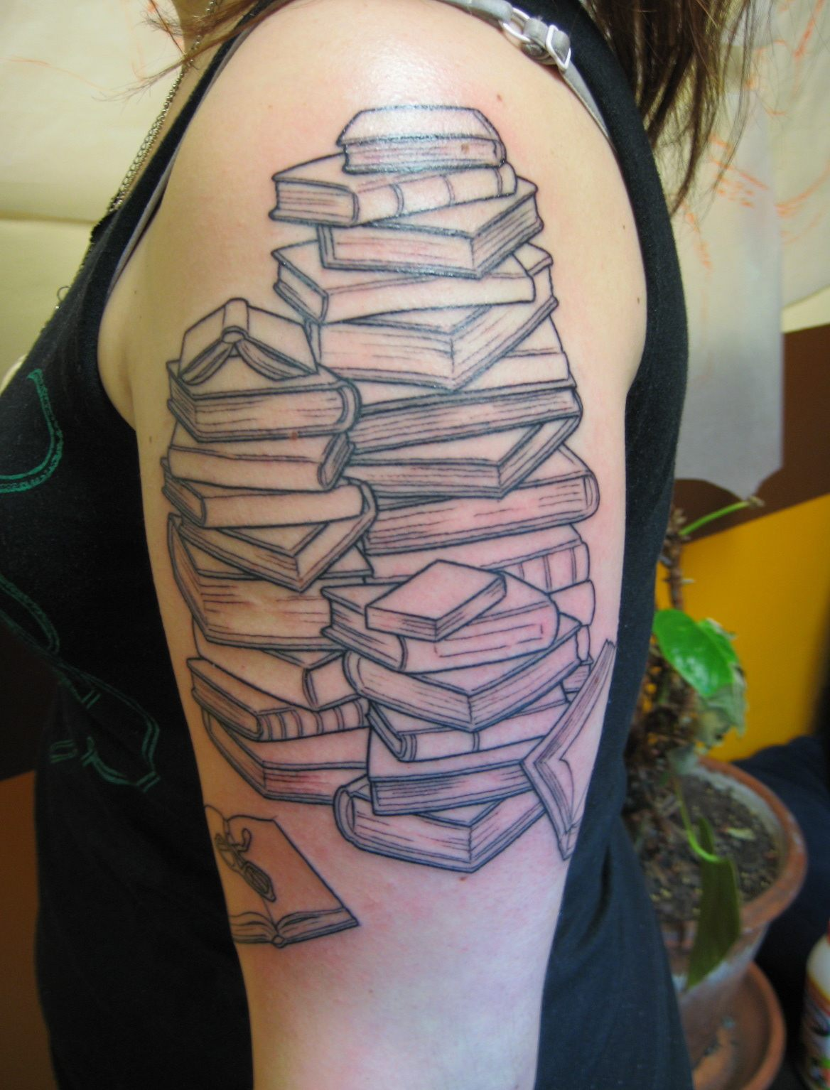 Stack Of Book Tattoo On Shoulder Of A Woman