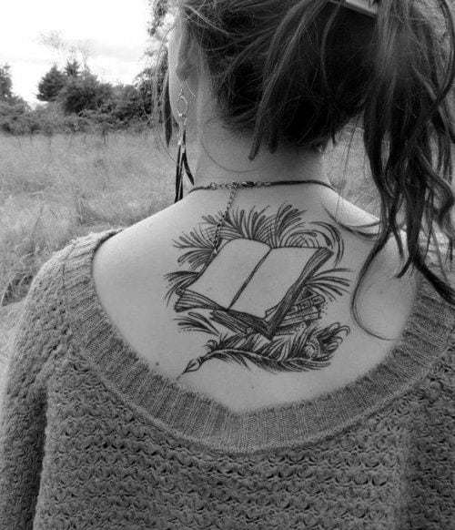 Open Book With Peacock Feather And Leaves Tattoo On Back Of A Woman