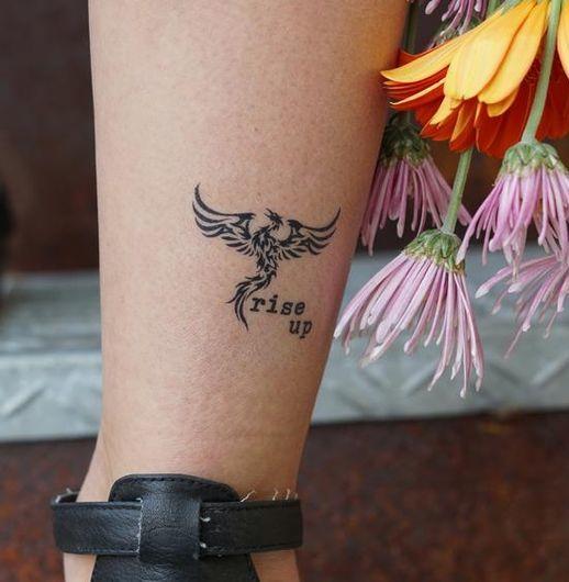 Phoenix Tattoo and 'Rise Up' written on leg.