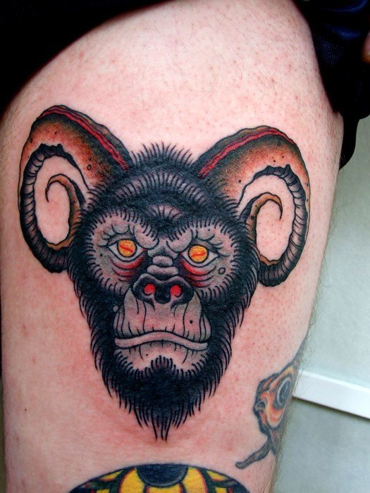 Bold Looking ape with horns tattoo on leg