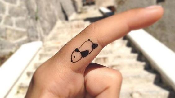 Tiny Panda tattoo on finger