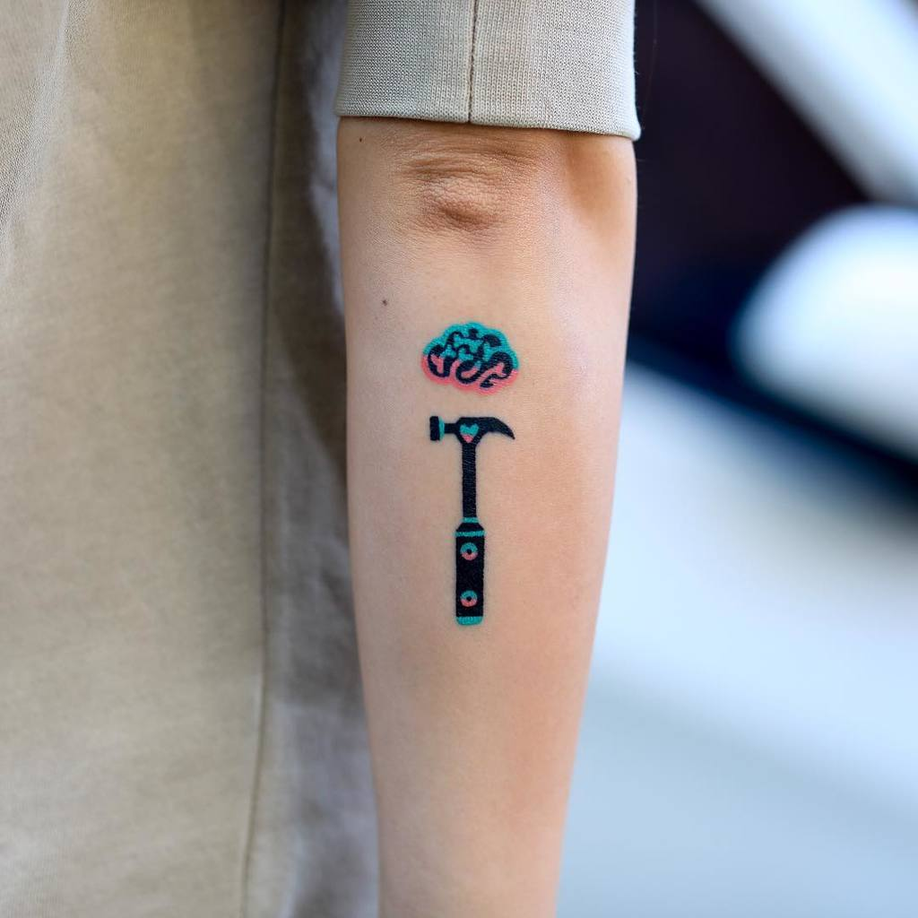Hammer and Brain tattoo on hand for women